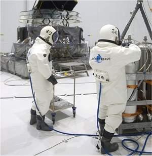 """Os """"frentistas espaciais"""" da ESA, vestidos a caráter para abastecer o telescópio espacial Planck, visto ao fundo. [Imagem: ESA-CNES-Arianespace]"""
